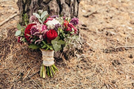 Rustic wedding bouquet with red rose nearly pine tree with cope space