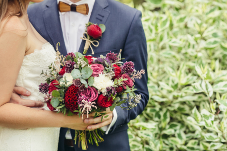 hand holding flower: groom with wooden bow-tie and red boutonniere hug bride with lilac wedding bouquet