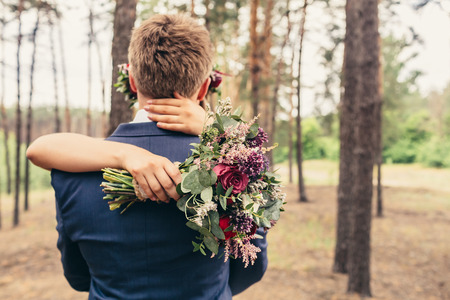 bride hug groom with lilac roses bouquet on wedding ceremony in forest