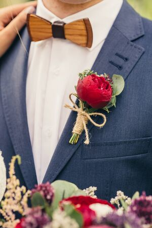lapels: grooms with wooden bow-tie and red rose boutonniere on wedding day Stock Photo
