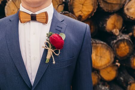 lapels: grooms with wooden bow-tie and red rose boutonniere on wooden background