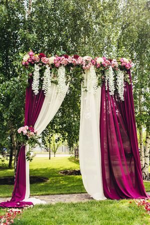 lilac flowers: lilac wedding arch with flowers on ceremony place Stock Photo