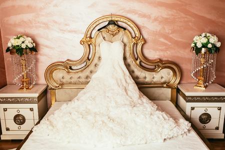 stylishness: wedding dress hanging on luxury bed decorated with flowers Stock Photo