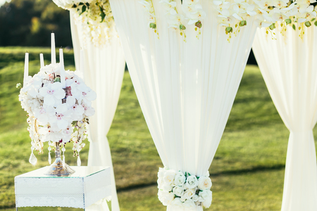 wedding arch with flowers and andle decoration on sunny day in ceremony place