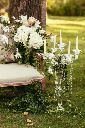 luxury wedding decorations with bench, candle and flowers compisition on ceremony place Foto de archivo