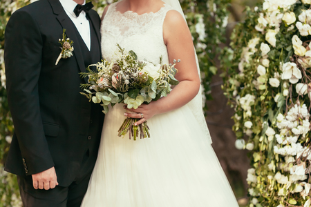 groom in black suit and bride in white wedding dress with rustic bouquet on wedding ceremony outdoor