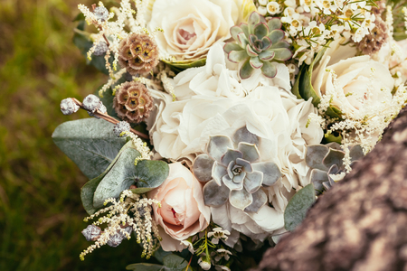 roses, succulents and other flowers in wedding bouquet on green grass and wooden texture