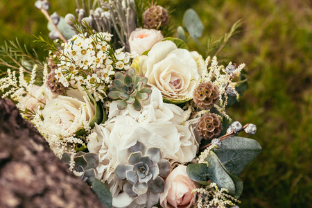wedding bouquet with roses and succulents on green grass and wooden texture