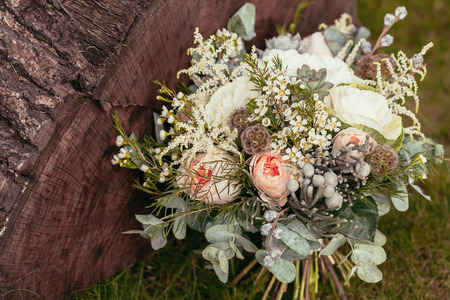 rustic wedding bouquet with roses and succulents on green grass and wooden texture Imagens - 51919458