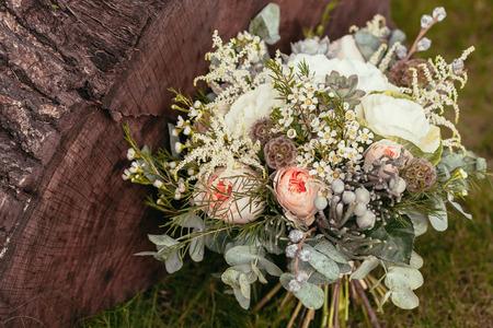 rustieke bruiloft boeket met rozen en vetplanten op groen gras en houten structuur