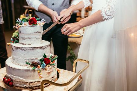 mariée et le marié coupe rustique gâteau de mariage sur le banquet de mariage avec rose rouge et d'autres fleurs