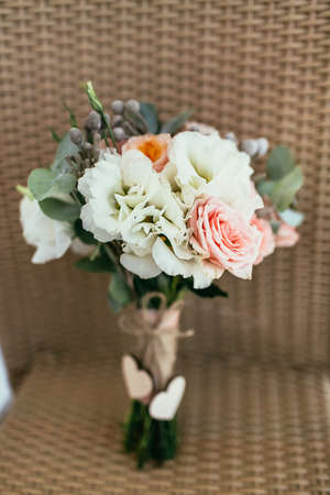 rustic wedding bouquet contain pink rose and other flowers with two wooden hearts