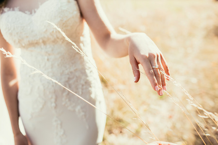 ear ring: beautiful wedding ring on bride hand touching ear on field in sunny day Stock Photo