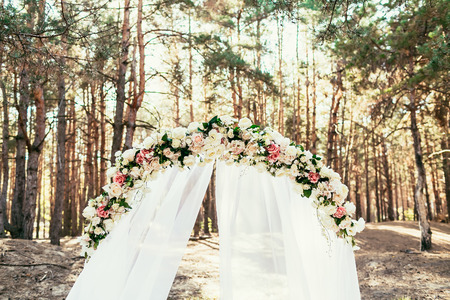 wedding arch with flowers situated in forest on Wedding ceremony