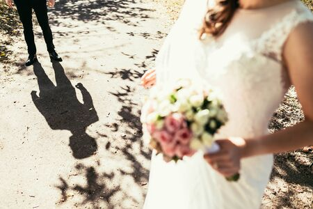 nearly: grooms shadow nearly bride with wedding bouquet