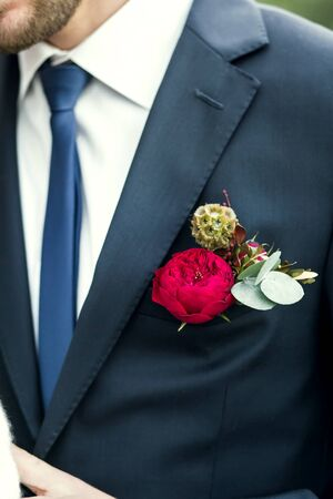 lapels: grooms with blue tie and red rose boutonniere on wedding day