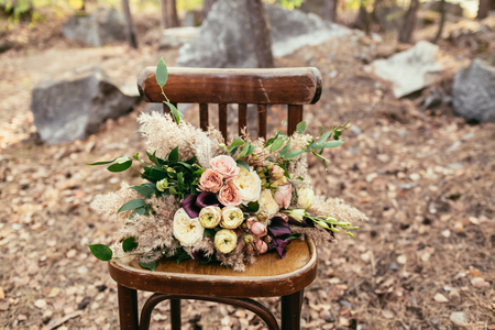 Bridal bouquet. The bride's bouquet. Beautiful bouquet of white, purple, pink flowers and greenery, lies on vintage wooden chair