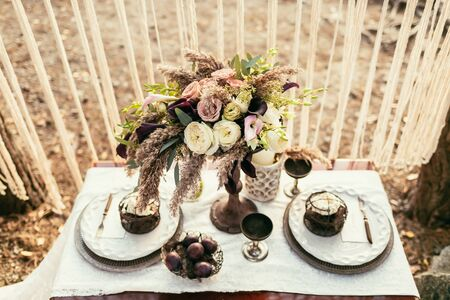 wedding served table. composition of different flowers in area of wedding party. Floral arrangement.