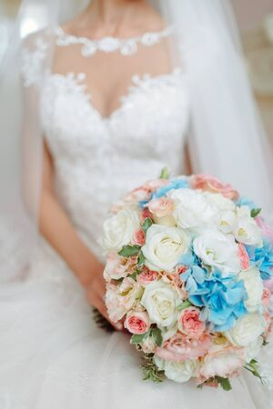 0be26dab4fe Bride in dress on bed holding wedding bouquet Stock Photo