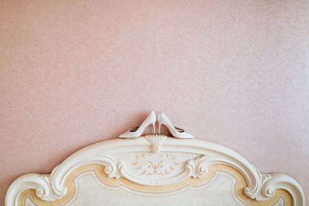 bedhead: Ivory wedding shoes for women stand on bedhead close to pink wall. Stock Photo