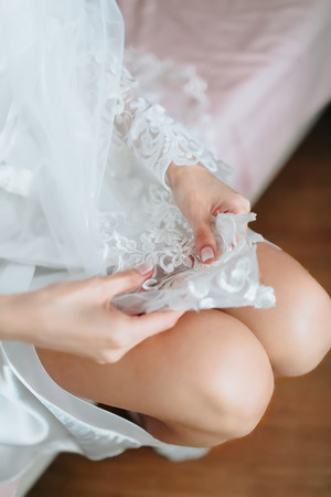 bed skirt: Beautiful legs. Brides cute knees is. Sitting on bed and looking on lace.