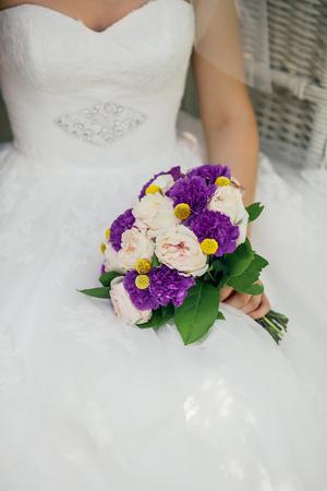 Bride holding delicate marriage bouquet