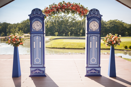 Beautiful wedding archway. Arch like clocks decorated with peachy flowers Stock Photo