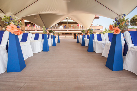 Beautifuly decorated with white and blue cloth and flowers chairs