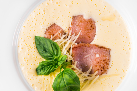 Cream soup with basil, meat steak and cheese on plate. Stock Photo
