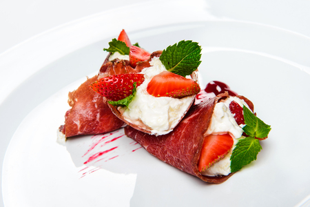 Strawberry and mint in white cream covered with sliced jamon.