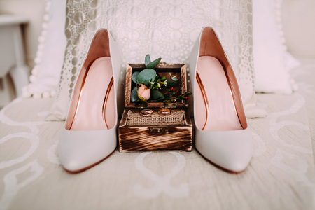 Wooden box with gold wedding rings and flowers stand next to elegant bridal shoes Stock Photo