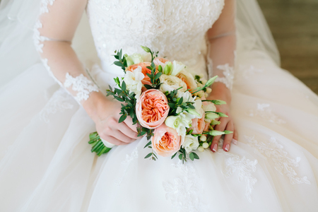 Gorgeous bouquet of white and orange flowers in the hands of the charming bride in a white dress. Close-up