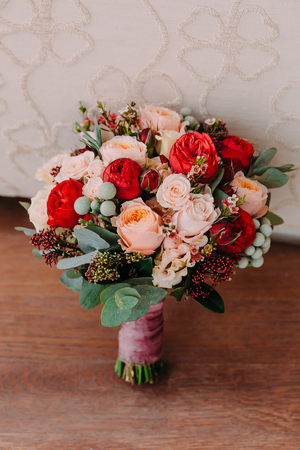 Beautiful wedding bouquet of red flowers, pink flowers, and greenery stand on the wall background