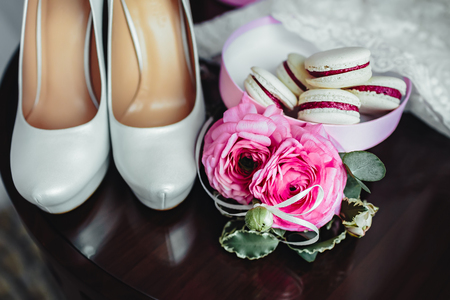 pinky: Wedding details, decoration. Bouquet of pink roses, bridal accessories and macaroons stand on a wooden table. Soft focus on roses. Close-up