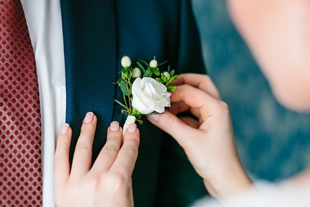 pinning: Close up brides hands pinning boutonniere to groom jacket. Wedding preparation