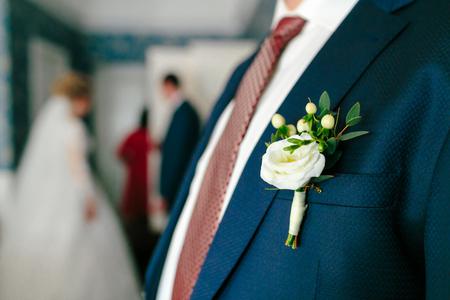 白のブートニアは、新郎のジャケットに固定。結婚式の準備。クローズ アップ