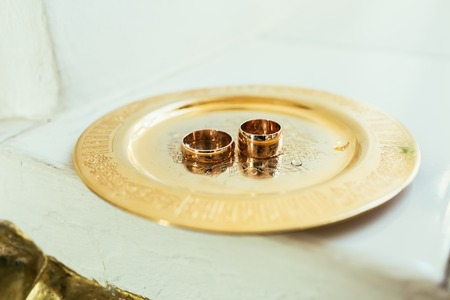 christian marriage: Golden wedding rings on the golden plate on a wedding ceremony in the church. Close-up