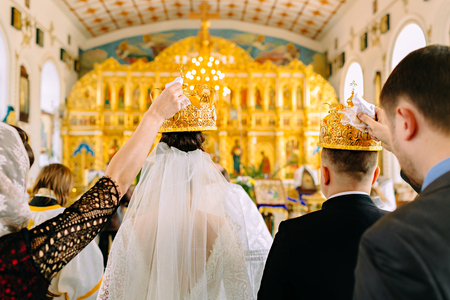 The witnesses of the newlyweds hold the golden crowns in the church over the heads of the bride and groom. Back view