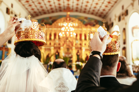 Wedding ceremony bride and groom in the Orthodox Church. Witnesses hold crowns over the heads of the newlyweds. Close-up, back view