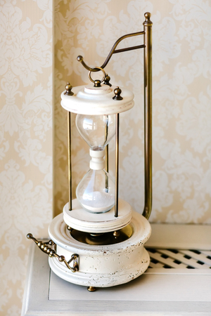 Vintage things. White old style wooden sand clock. Interior ideas. Time concept