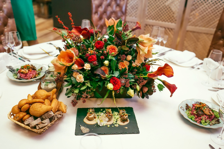 Table decor with a beatiful flowers. Elegant wedding banquet decoration. Close-up Stock Photo