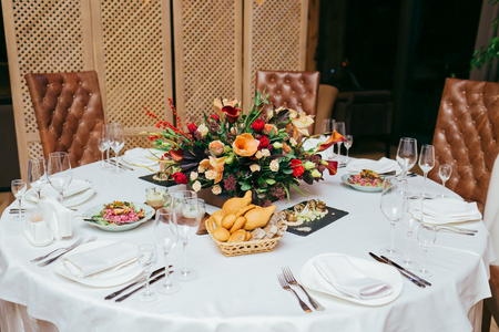 Festive table served with dishes and decorated with branches of greenery.