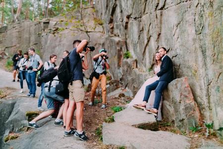 A group of paparazzi people taking pictures of a wedding couple man in nature. Selective soft focus on the photographers. Outdoor Editorial