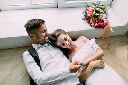 Cheerful newlyweds holding hands and lie on the floor next to bridal bouquet. Artwork. Wedding morning. Soft focus. Top view