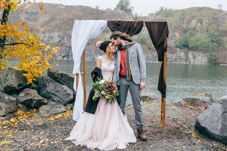 Stylish bride and groom with dreadlocks are holding hands next to wedding arch. Autumn wedding ceremony outdoors. Happy newlyweds. Full length portrait