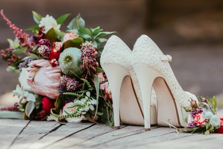white bridal shoes and rustic wedding bouquet with white and bordeaux roses, peonies, poppy and greens on an aged wooden floor. Artwork, selective focus Banco de Imagens