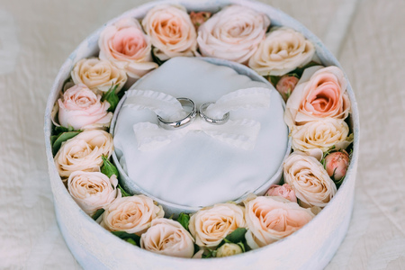 Wedding rings on white background in a pink round box with peach roses. Artwork. Soft focus. Top view