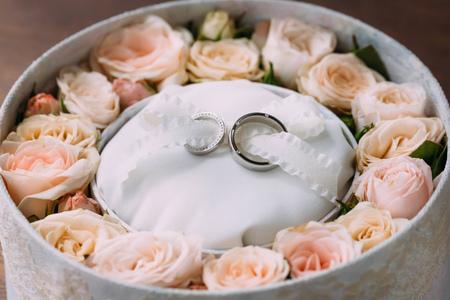 Trouwringen op witte achtergrond in een roze ronde doos met perzikrozen. Artwork. Soft focus. Zijaanzicht