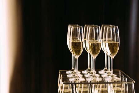 Champagne glasses standing in a tower at the party on a dark background. Artwork. Copy space for text