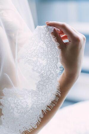 Elegant brides hand with a white lace veil. Artwork Wedding concept. Close-up image, soft focus Stock Photo